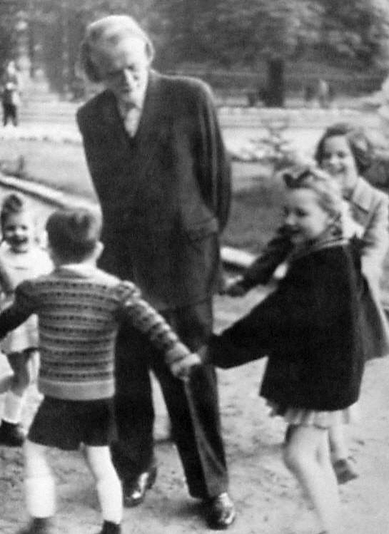 Zoltan Kodaly standing in the middle of a circle of young children playing a singing game